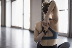 Woman in a yoga pose, stretching the deltoid muscle