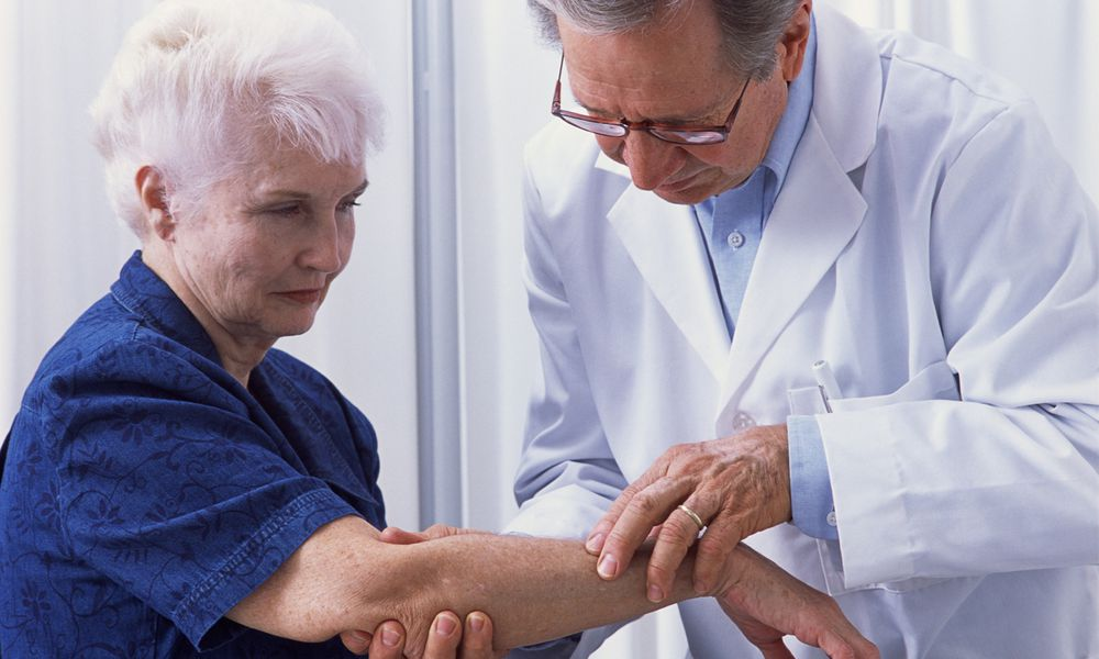Dermatologist examining woman's skin