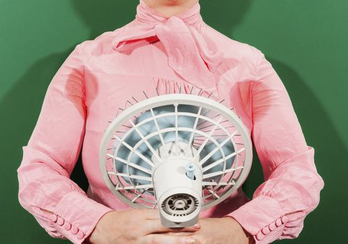 A woman uses an electric fan to dry sweat stains on her shirt.