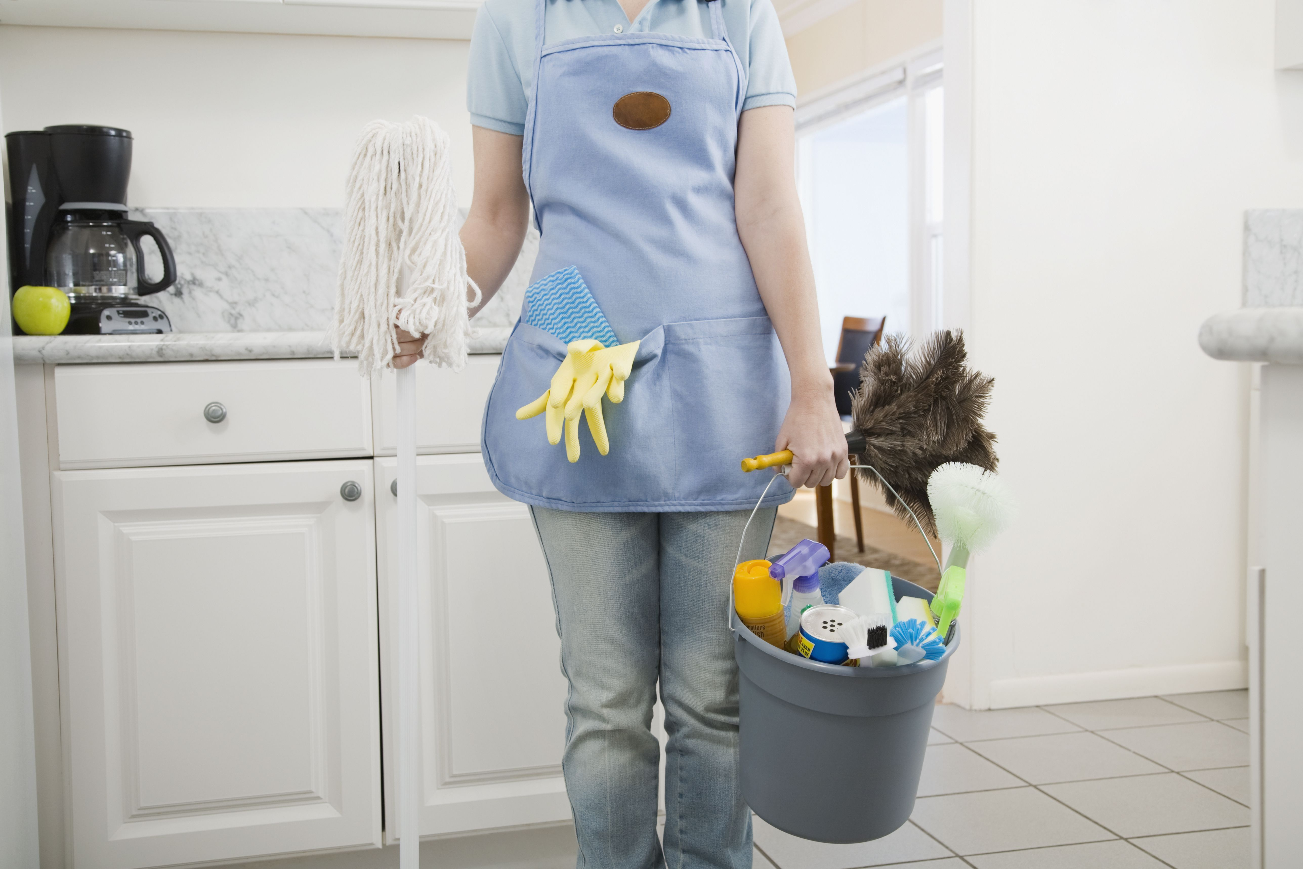 Woman holding mop and cleaning supplies