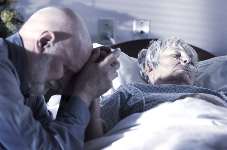 Man holding patient's hand.