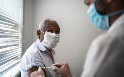Black older man receiving a vaccine shot.