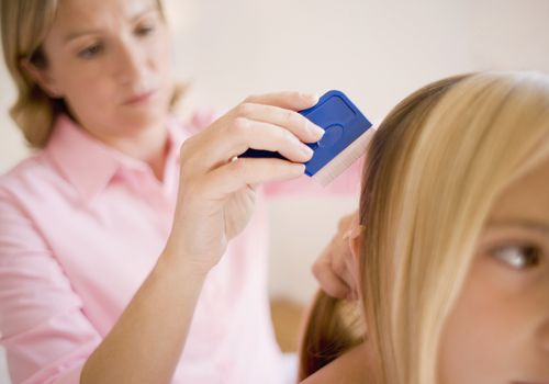 Mother combs daughter's hair with a lice comb