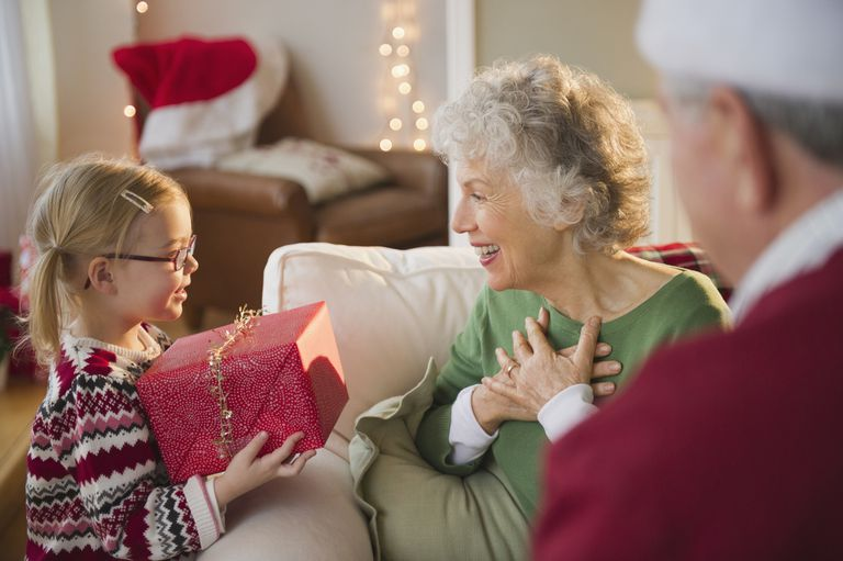 Granddaughter giving Christmas present to Grandma - stock photo