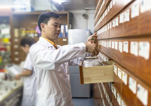 A Chinese male doctor weighs traditional Chinese medicine