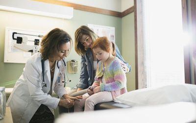 Pediatrician checking reflexes of girl in examination room