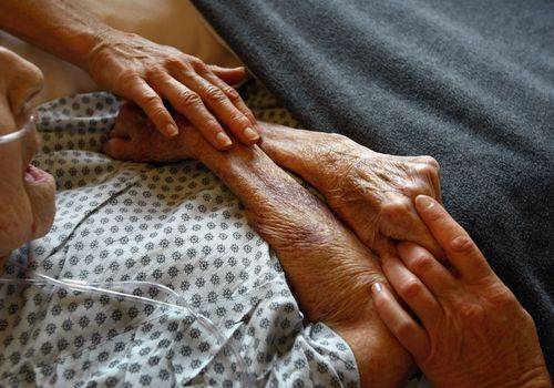 Senior man in hospital with people holding both his hands