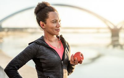 Woman in athletic gear holding an apple