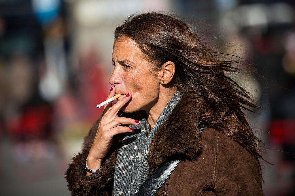 Woman walking outside smoking a cigarette
