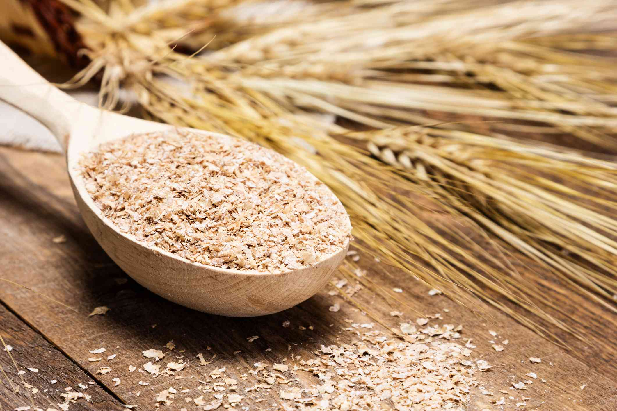Close-up of wooden spoon filled with wheat bran