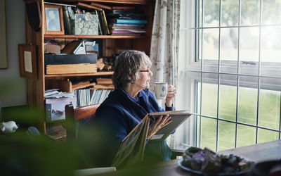 An older woman looking at the window, remembering