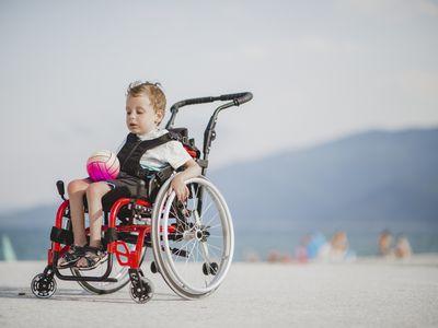 Boy in wheel chair holding a ball
