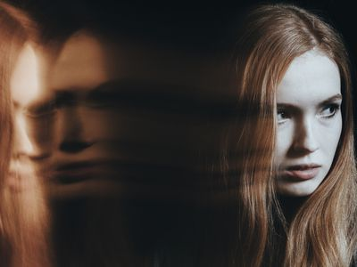 Women's face half in shadow looking to her side with blurred reflections of her face on her left