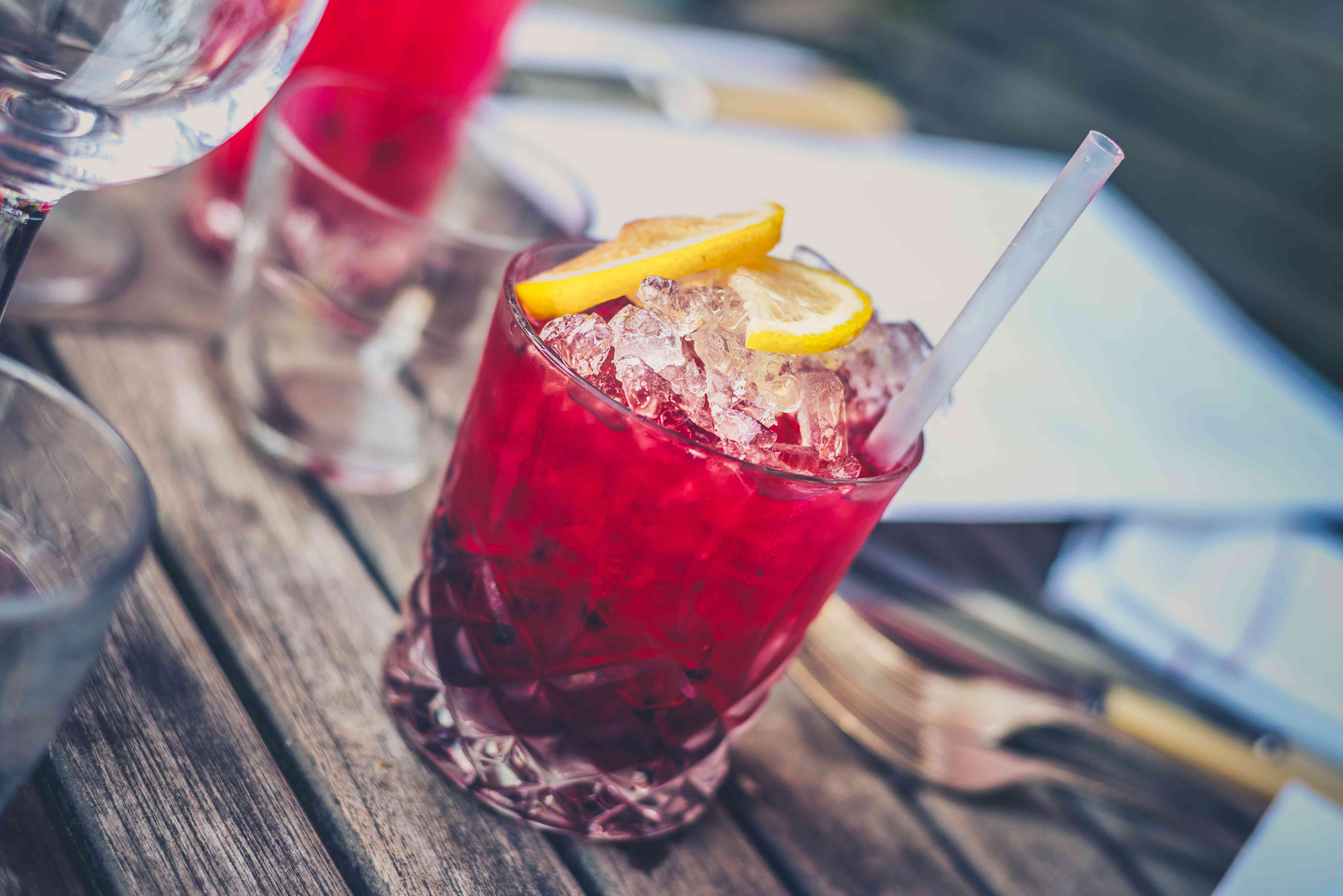 A glass of cranberry juice with ice, orange wedges, and a straw on a picnic table.