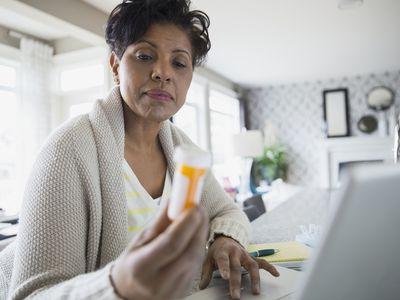 Older black woman looking at a prescription drug bottle