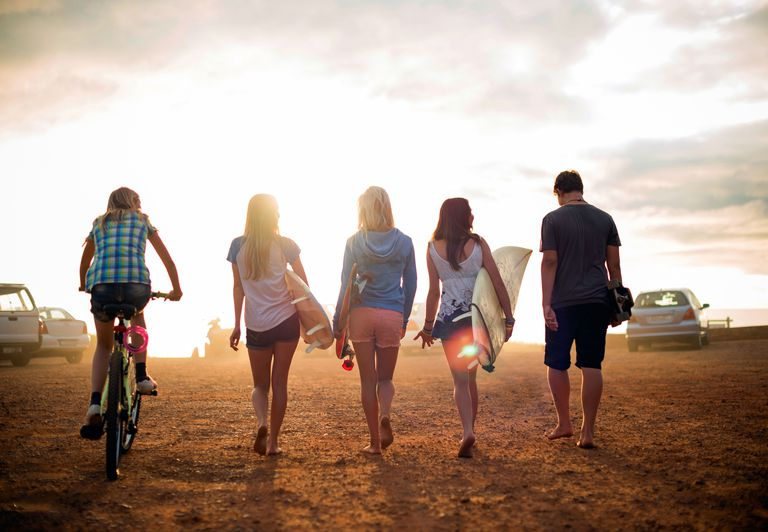 Rear view of five friends going to beach