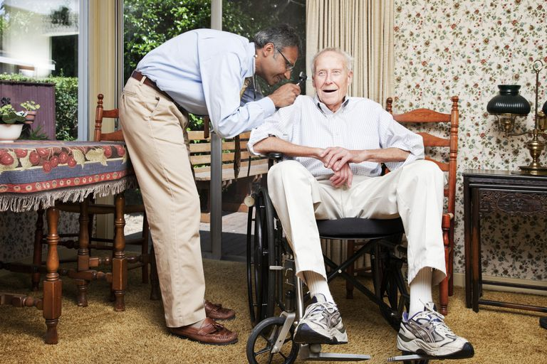 Doctor examining man in a wheel chair in his home