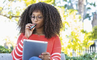 Woman smoking electronic cigarette while using digital tablet in public park - stock photo