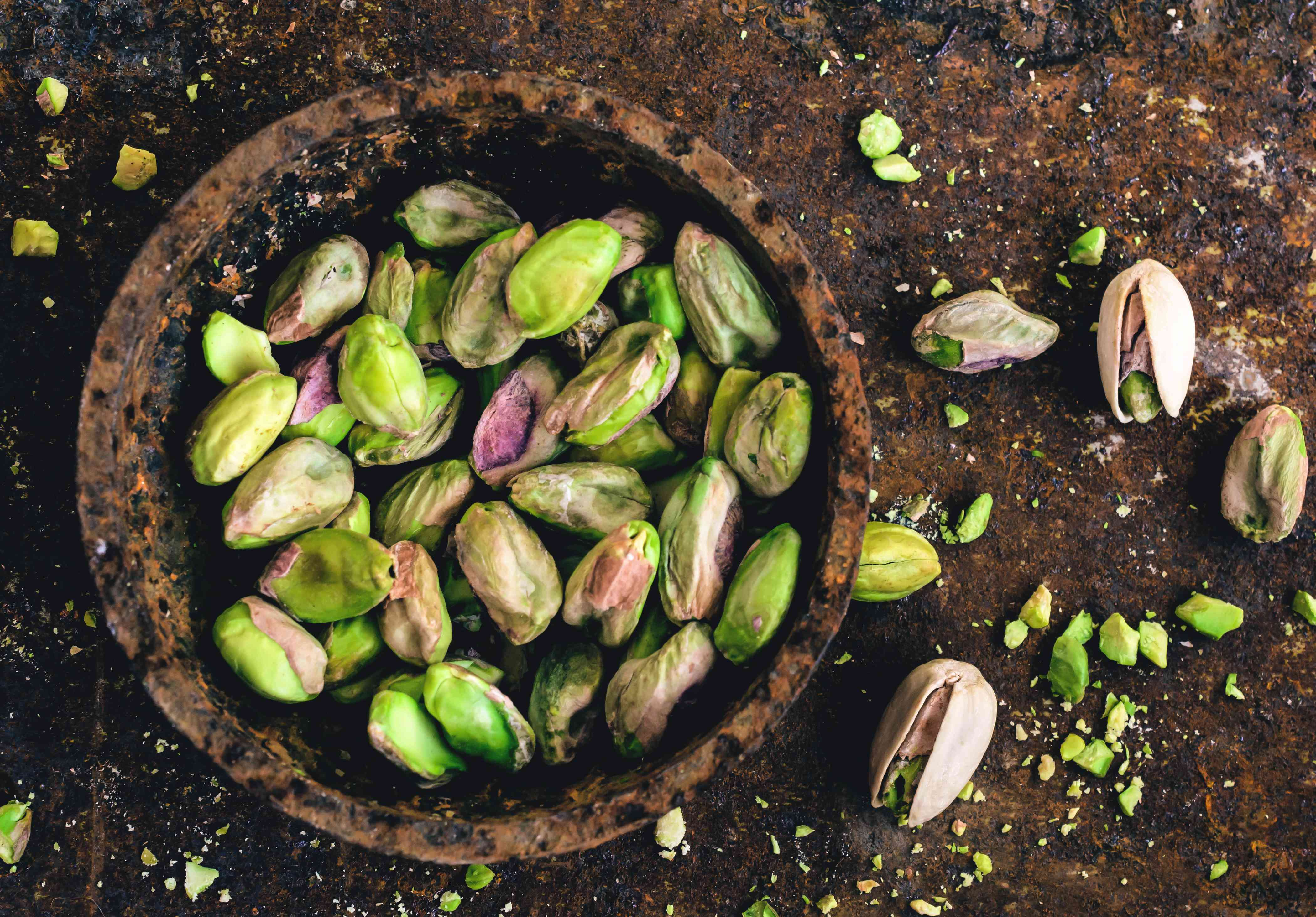 Pistachio nuts in a bowl sitting on the ground
