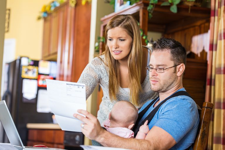 Concerned couple holding a baby and looking at a bill