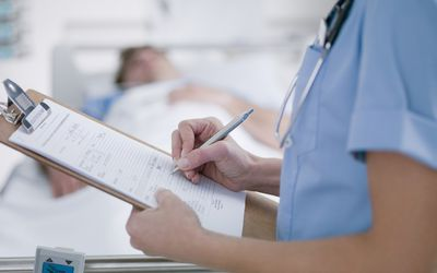 nurse writing on clipboard and man in hospital bed in the background