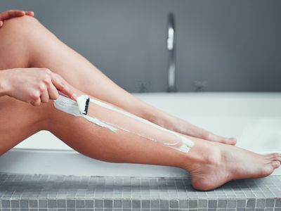 A woman shaving her legs by the bath tub