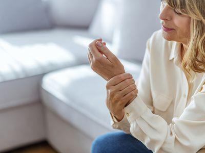 Senior woman suffering from pain in hand at home