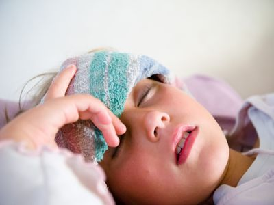 young girl with a washcloth on her forehead
