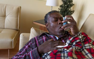 An older man with problems with the respiratory system is using an inhaler at home while lying down on the sofa.
