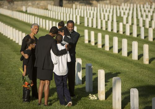 Multi-generation Black family hugging in military cemetery