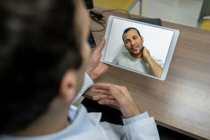 Patient on a video call with a doctor through a tablet computer