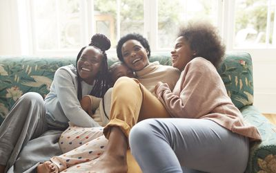 Portrait of happy woman embracing girls at home