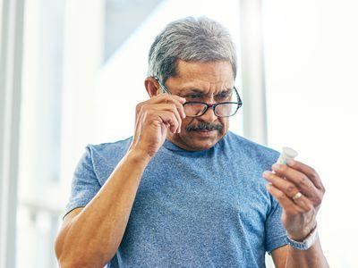 Man looking at prescription bottle