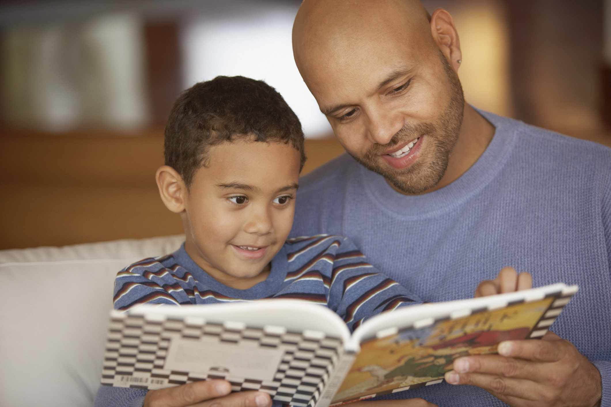 Father reads with son on couch