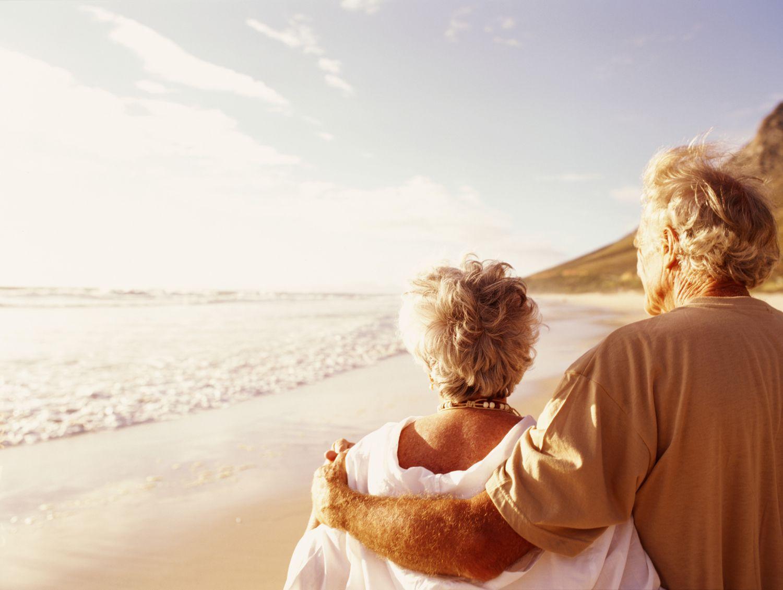 Senior couple embracing on beach, rear view
