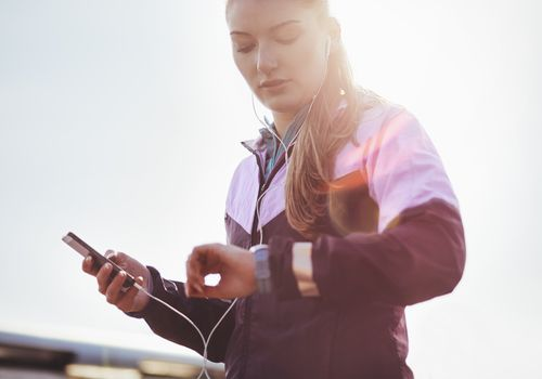 young woman runner syncing smartphone and watch