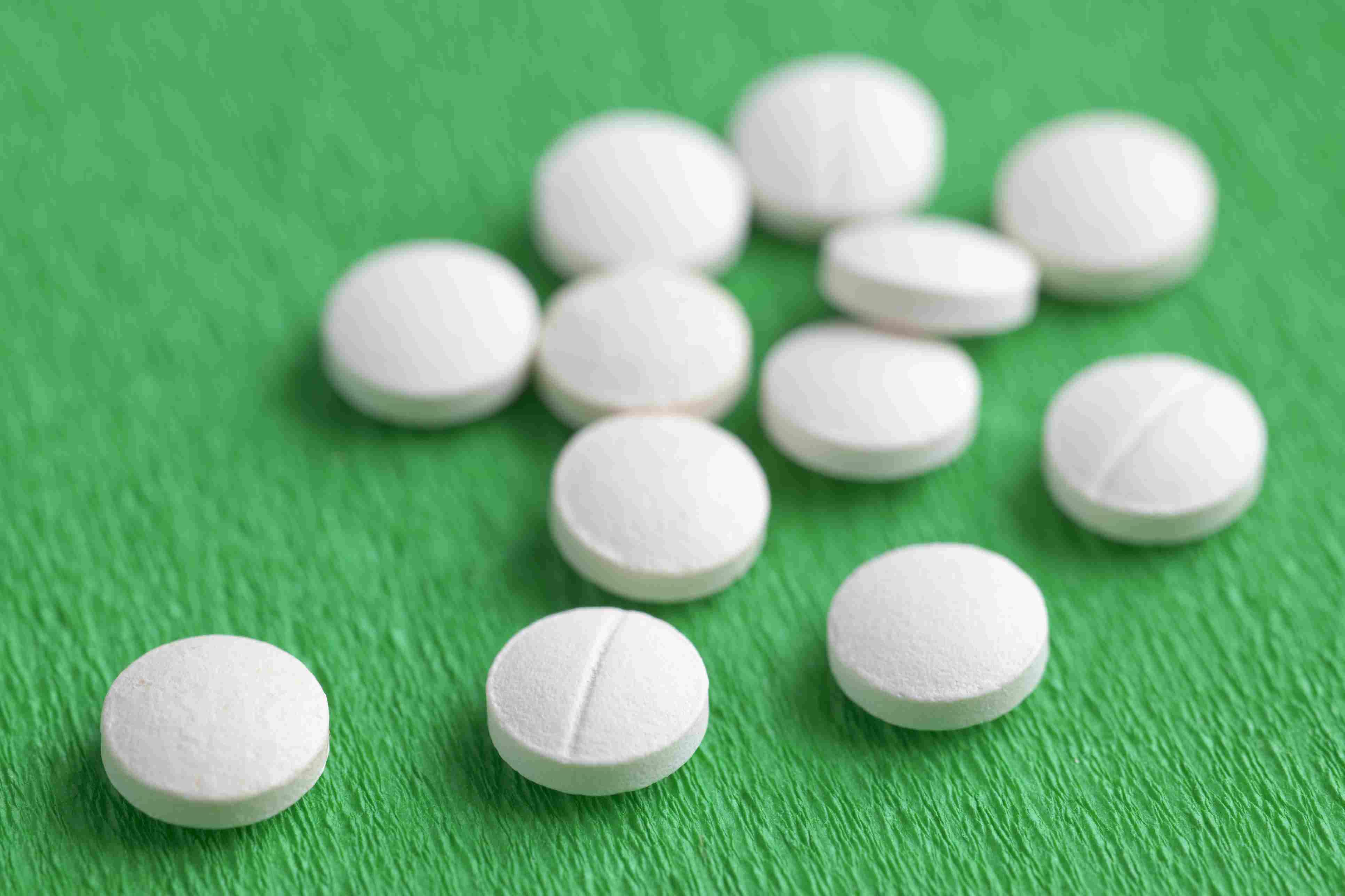 White Melatonin Natural Medicine Sleeping Pills on Green Background
