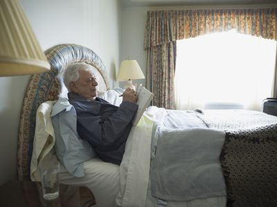 Older man sitting up in bed writing in his journal
