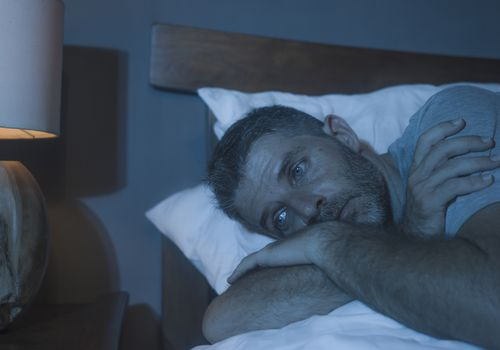 Middle-aged man awake in bed in the middle of the night.