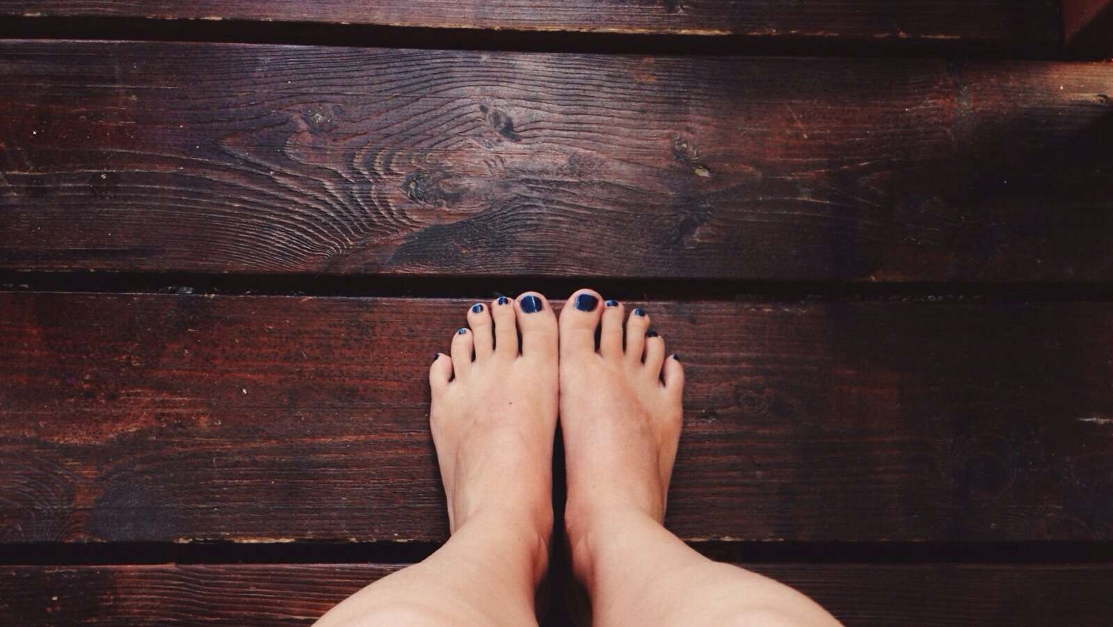 Feet with painted toenails on a wooden floor