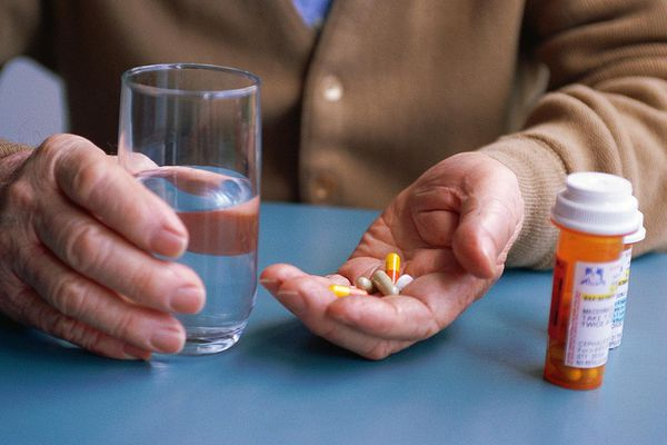 Hands holding a glass of water and pills