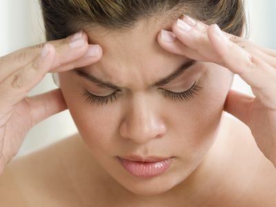 A woman holding her forehead in pain