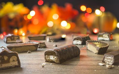 Candy bars cut in half, some containing nuts or nut butter, with a fall/autumn/Halloween lighted background.