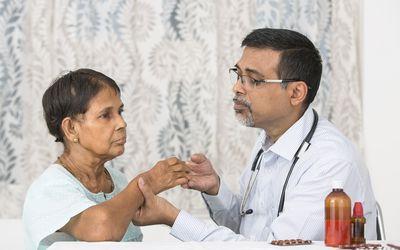 mature doctor examining a rheumatoid arthritis patient