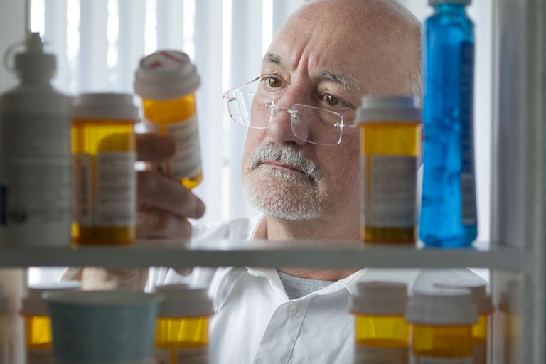 Man looking at prescriptions in medicine cabinet