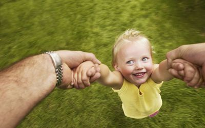 adult man swinging young girl by her arms