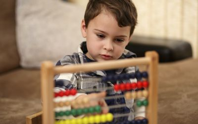 A young boy using an abacus with a blurry background