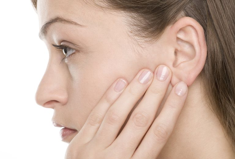 Woman holding her ear in pain