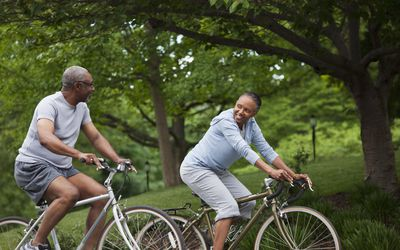 Older couple riding bikes in the park