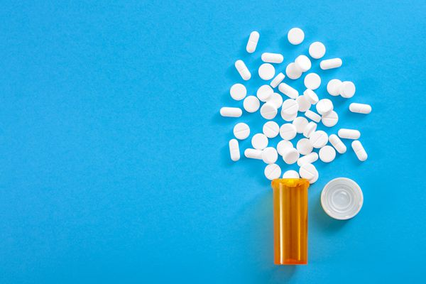 Pills falling from pill bottle on blue background